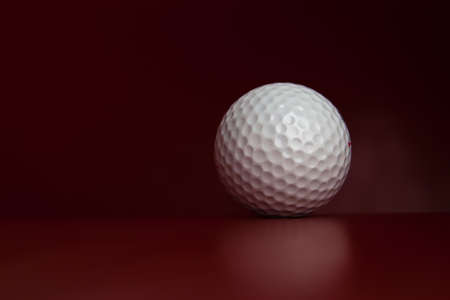 White golf ball lying on red leather green