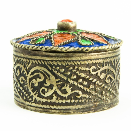 A small round metal jewel casket with an antique look. The casket is seen from the side. photo