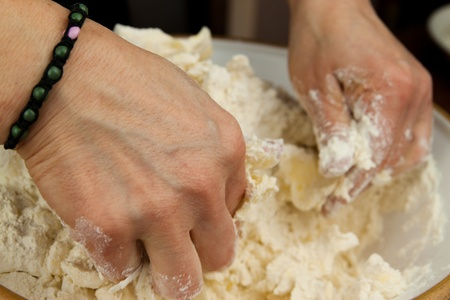 A cook is mixing a bowl of of butter and flour dough with her hands photo