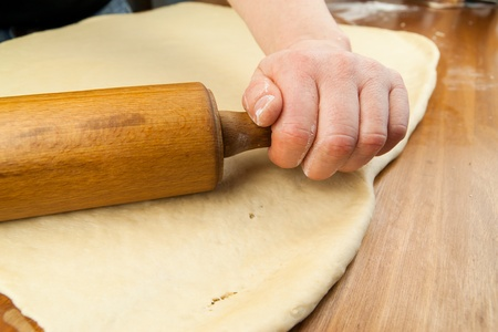 A cook is rolling out fresh dough with a rolling pin on a hardwood surface