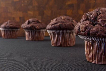 Four chocolate muffins on a dark surface photo