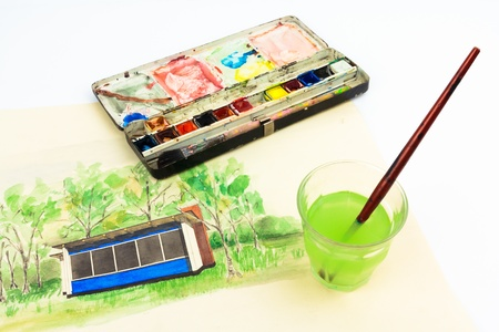 Watercolor painting, watercolor box and brush in water photo