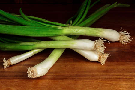 Leeks lying in a pile on a hardwood surface