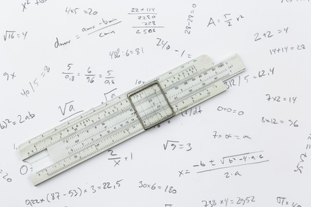 Slide rule lying on a piece of paper with handwritten calculations Stock Photo