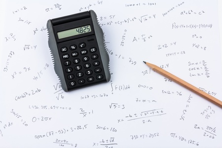 Pocket calculator and pencil on a paer full of calculations Stock Photo
