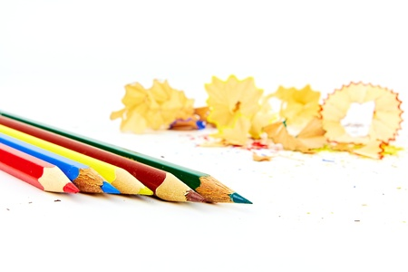 Five colored pencils in front of a bunch of shavings Stock Photo