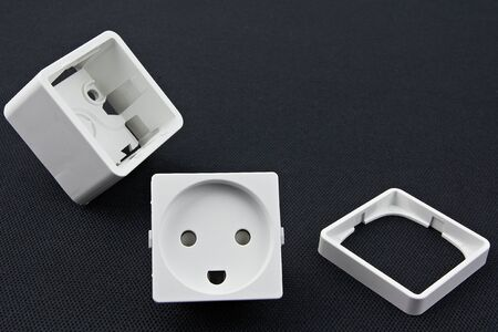 dismantled: Dismantled electrical outlet lying on a black surface