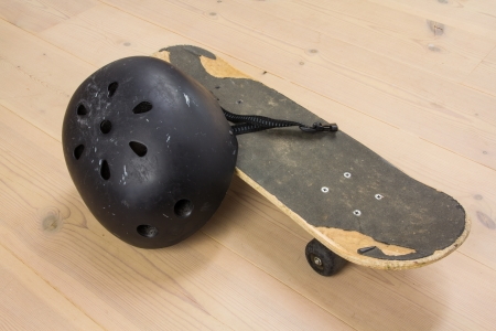 Skateboard and protective helmet on a wooden floor photo