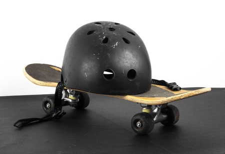 Old skateboard and worn helmet on black and white background photo