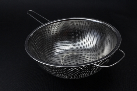 Stainless sieve on a black background