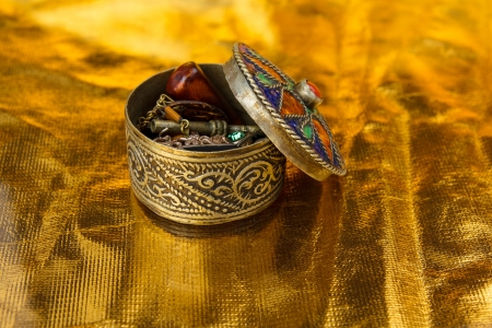 A small round metal jewel casket with an antique look. The colored lit is taken off revealing som jewels inside.