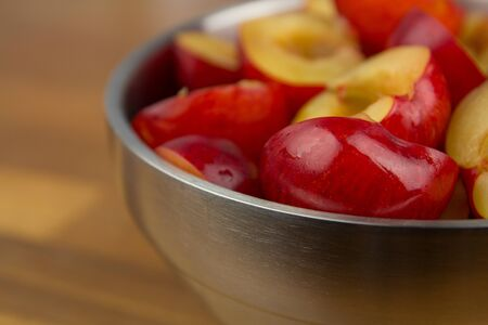Close up of a bowl of red plums on a wooden table Stock Photo