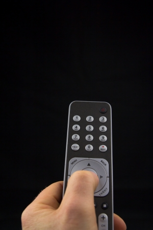 Hand pressing a button on a remote controll Stock Photo