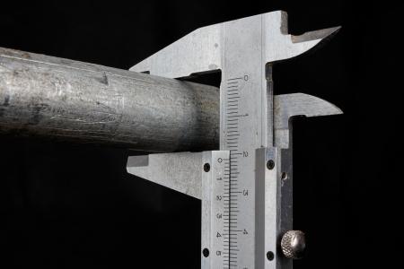 vernier caliper: Vernier caliper measuring a pipe on black background