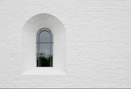Arched latticed window in a white church wall Stock Photo - 21048628