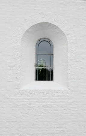 Arched latticed window in a white church wall Stock Photo - 21048633
