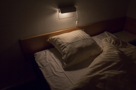 A bed in the dark with the quilt folded aside Stock Photo