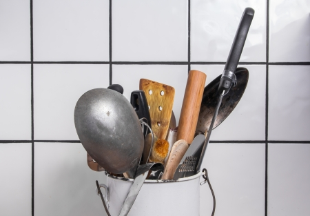 Enamel bucket with kitchen utensils photo