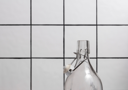 Glass bottle with flip top in front of a tile background photo