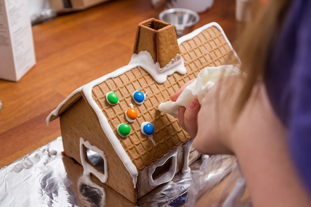 Decorating a gingerbread house with glacing from a syringe photo