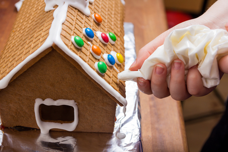 Decorating a gingerbread house with glacing from a syringe Stock Photo