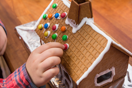 Decorating a gingerbread house with chocolate drops photo