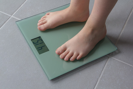 Child with bare feet on a bathroom scale of glass photo