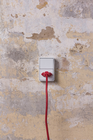 Red chord and plug in a white electrical socket photo