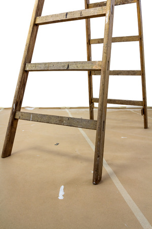 Bottom of a wood ladder on a paperboard covered floor photo