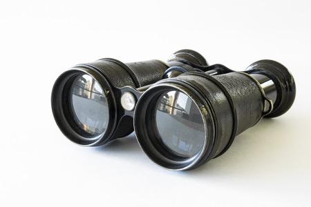 Black binocular lying on a white surface photo