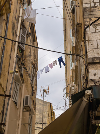 Narrow alley in Corfu Town with laundry hanging between buildings Stock Photo