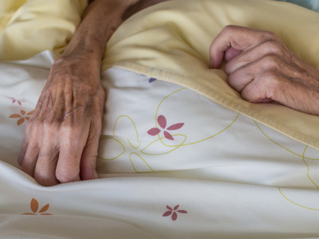 skinny: Las manos de una mujer muy vieja y flaca en la cama