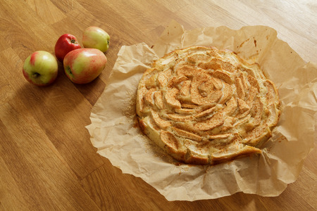newly baked: Newly baked apple pie on baking paper with apples lying next to it