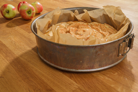 Newly baked apple pie in a metal springform with apples lying next to it