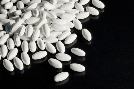 Pile of white pills on black surface