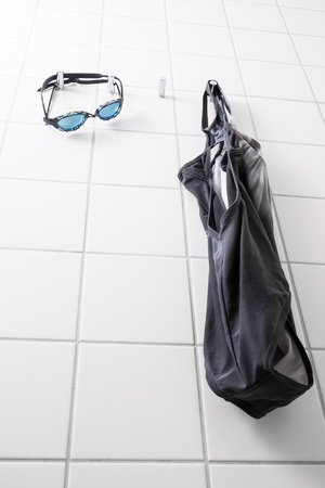 swim goggles: Blue swim goggles and a swimming suit hanging on hooks