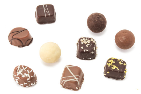 group of filled chocolates standing on a white surface