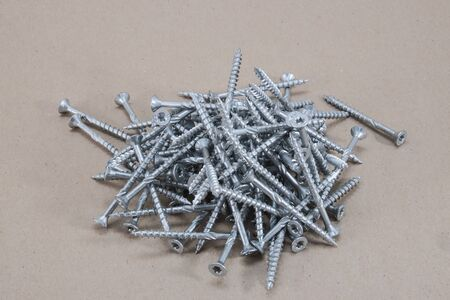 Long torx screws lying in a pile on a grey surface Stock Photo