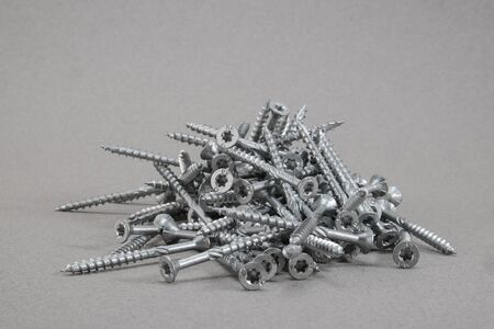 woodscrew: Wood torx screws lying in a pile on a gray surface