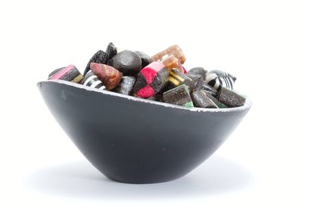 liquorice: Black candy bowl filled with liquorice candy Stock Photo