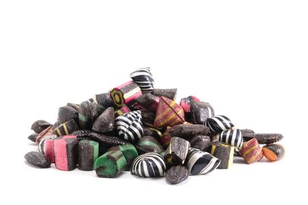 liquorice: A bunch of assorted liquorice hard candies on an all white surface
