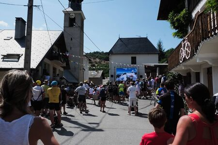 big screen: people gathered in a small town square to watch tour de france 2015 on a big screen before the riders actually passes the town