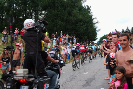 spectator: group of the 2015 tour de france cycling field riding through the spectator crowd near the top of Col du Mollard