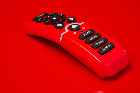 shiny buttons: remote control of red shiny plastic with black rubber buttons, lying on a red mirroring surface