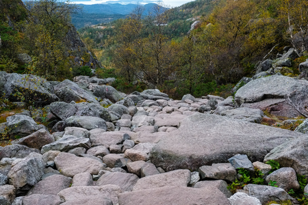 rockslide: rough rock paved pathway down a hill side towards trees, mountain tops are seen in the distance Stock Photo