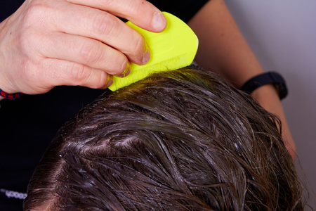 person checking wet hair for lice, with a yellow lice comb