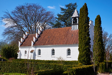 Classic danish small white chapel with a zinc covered belfry