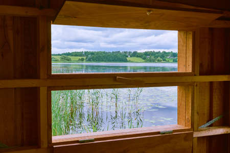 Lokking out over a lake to green grass fields on the hills at the lake Sjaelsoe shore in Birkeroed, denmark