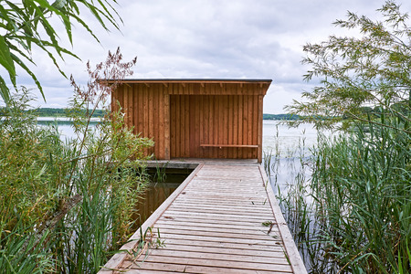 Birdwatch shelter with board on board wood cladding, at the end of a wooden jetty going out in the water of a lake in Birkeroed, Denmark