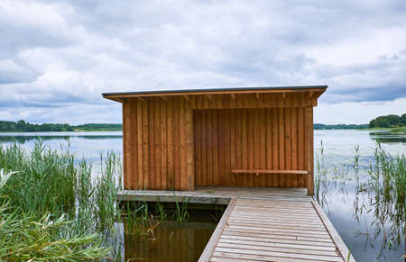 Birdwatch shelter made of wood, at the end of a wooden pier at the border of lake Sjaelsoe in Birkeroed, Denmark